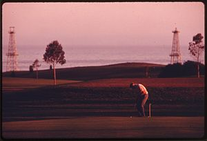 Ellwood Oil Field - Sandpiper Golf Course with derricks in background, 1975. Photo by Charles O'Rear.