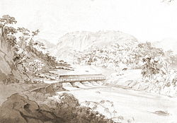 A pencil with wash sketch depicting a forested valley with riders and pack animals on a road on the left side which descends to a covered bridge across a river on the valley floor
