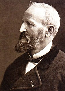 A Caucasian man in his 60s with thinning white hair and a greying moustache and beard, wearing a white shirt with an upturned collar, a thin dark bow tie, and a jacket of heavy material. He is facing left.