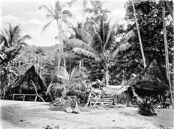 Black and white photograph of a village of huts amongst palm trees with a heavily wooded background. A man stands and a woman sits in the foreground.