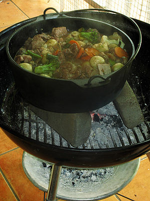 "South African cuisine - Potjiekos, literally translated ""small pot food"", is a stew prepared outdoors in a traditional round, cast iron, three-legged pot. This one is being cooked on a barbecue."