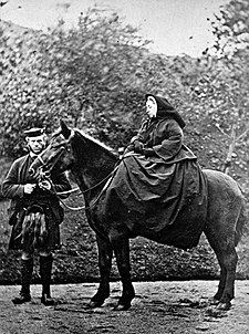 A woman, severely  dressed in black, seated on a horse with a man standing by its head.