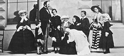 Photograph of a seated Victoria, dressed in black, holding an infant with her children and Prince Albert standing around her