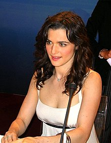 Weisz seated in front of a microphone