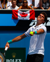 Raonic looks up in the air, his racquet pointing down in his left hand and a ball cradled in his right hand. In the background, a spectator holds a Canadian flag.