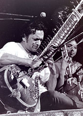 Black and white photograph of a man playing Sitar.