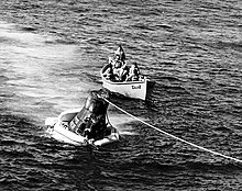 A conical black spacecraft, with its base surrounded by inflated bags, floating in the water; a rope runs from the top of the spacecraft to the edge of the photograph. A small boat, with a group of men in it is just behind the spacecraft.