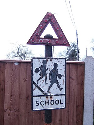 Warning sign - Pre-standardization British School Zone with metal-cutout generic Warning symbol embellished with red glass reflector-spheres.