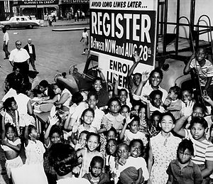 Voter registration in the United States - A group of African American children gather around a sign and booth to register voters. Early 1960s.