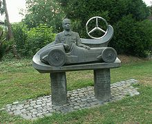 A bust of Caracciola sits behind a statue of a single-seater racing car; the Mercedes three pointed-star is beside that.