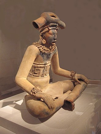 """Remojadas - A large terracotta figurine of a young chieftain in the Remojadas style.  In his 1957 book on Mesoamerican art, Miguel Covarrubias speaks of Remojadas' """"magnificent hollow figures with expressive faces, in majestic postures and wearing elaborate paraphernalia indicated by added clay elements."""" 300 - 600 CE; Height: 31 in (79 cm)."""