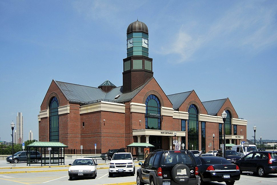 Three-story brick building with three gables on roof; large clock tower made of green glass seen at center of left gable.