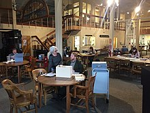 View of the reading room in the Maritime Research Center showing researchers, NPS uniformed staff as well as visitors, at tables consulting archives, books, and audio materials, Reference Librarian Gina Bardi at the Reference Desk in the background.