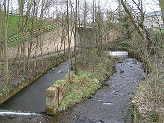 """River Sett - The Sett passes under the A624 Hayfield """"bypass"""". The tower of St. Matthew's church can be seen through the trees in the background, and in the foreground are the scanty remains of Walk Mill."""