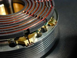 Helical scan - The rotating portion of the head drum showing the rotary transformer and three of the six tape heads used in this particular VCR