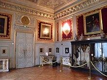 Angle d'une salle décorée de boiseries blanches, de tableaux en hauteur et comprenant une grande vitrine à droite