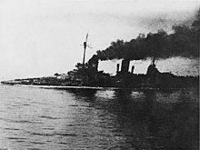 "A large gray warship, heavily flooded; its deck is nearly submerged. Thick black smoke pours from the funnels. An in-photo caption reads: ""Seydlitz nach der Skaggerack-schlacht"", or ""Seydlitz after the Skaggerak battle."""