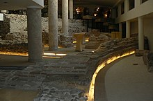Columns and Roman brick and stone ruins on the ground floor of a hotel lit by yellow lighting