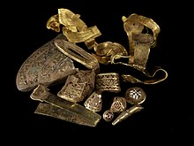 A selection of highlight pieces from the Staffordshire Hoard (top) and a gold sword hilt fitting with cloisonné garnet inlay (below), uncleaned by conservators, still showing traces of soil