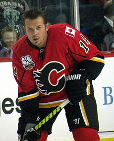 An ice hockey player stands partially crouched, leaning on his stick. He has short black hair and is not wearing a helmet. He is wearing a red uniform with a large black C on his chest.