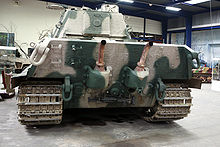 The overhanging rear face of a large tank, two laterally spaced exhaust pipes protrude from mountings, pointing upwards, curving away from the vehicle at their ends.
