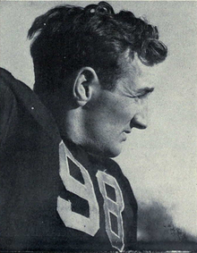 A football player wearing a dark jersey with the number 98 on it.