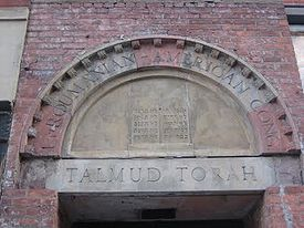 """Stones over a doorway arch with the incomplete name """"Roumanian-American Cong"""" in carved capital letters. Beneath, carved into the lintel, are the words """"Talmud Torah"""", also in capital letters. The two surround a carving of two tablets with Hebrew writing, representing the Ten Commandments."""