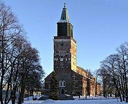 """Åbo domkirke i december 2004.   Dens nuværende største længde er 89,1 m, bredt omkring 40 m og forhøjet 44,5 m.   Tårnets højde over det foran det liggende torvs niveau er 95,6 m og over Aura på 104 m.   Dens tårnscepter blev opført efter branden i 1827 ifølge C. L. Engels tegninger og om hvilken Zacharias Topelius har digtet:   """"Da glitrer spidsen af det kobberklædte tårn.   Blåhvidte flammer, tindrende stjerner lige, omkring det gyldne kors skinne i nattens mørke, og tårnets fjedrende sorte skarer flykte."""""""