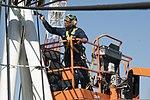 U.S. Navy Aviation Support Equipment Technician Seaman Richard Henry, center, paints a crash and salvage crane on the aircraft carrier USS George Washington (CVN 73) in Yokosuka, Japan, March 10, 2014 140310-N-IV489-033.jpg