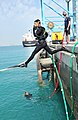 U.S. Navy Diver 3rd Class Tory Harding, assigned to Mobile Diving and Salvage Unit 2, steps off Hidd Pier to conduct a heavy lift inspection dive in Bahrain Feb 130224-N-CG436-037.jpg