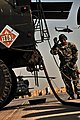 US Army 52918 CAMP TAJI, Iraq-Spc. Kanedria Wilson, from Louisville, Ky., a petroleum supply specialist, signals that fuel has started to flow from the refuel truck to the AH-64D Apache attack helicopter, here, Oct.jpg