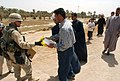 US Navy 030405-A-0000F-002 Capt. Jimmie Cummings of the 49th Public Affairs Detachment hands an Iraqi man a humanitarian ration, during a humanitarian assistance mission conducted by the 82nd Airborne Division in central Iraq.jpg