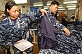 US Navy 050112-N-9849W-001 Yeoman 1st Class Latricia Perkins, left, assigned to the Administration Department on board Naval Air Facility Atsugi, Japan, sorts through a pile of the new Navy Working Uniforms.jpg