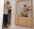 US Navy 060306-N-5345W-085 Aviation Structural Mechanic 3rd Class Joshua Corl, left, and Machinist's Mate 2nd Class David Gayton spackle the walls in a Gulfport home, while preparing the interior for repainting.jpg