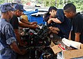 US Navy 070811-N-4021H-068 Sailors from USS Pearl Harbor (LSD 52) alongside Sailors from the Nicaraguan Navy, repair a small out-board engine while participating in a subject matter expert exchange during Partnership of the Ame.jpg