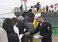 US Navy 071027-N-9520G-005 Electronics Technician 2nd Class Adam Haupt hands out welcome aboard pamphlets as hundreds of visitors from the Hokkaido area line up for a chance to tour guided-missile destroyer USS Fitzgerald (DDG.jpg