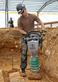 US Navy 071217-N-8547M-043 uilder 2nd Class Lance D. Fairchild of Naval Mobile Construction Battalion (NMCB) 5 packs the loose dirt after setting the elevation for footers.jpg