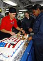 US Navy 090213-N-6233C-028 Culinary Specialist 3rd Class Paul Valdez serves birthday cake to Sailors aboard the aircraft carrier USS George Washington (CVN 73).jpg