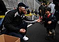 US Navy 091205-N-6233H-097 Hull Technician 3rd Class Kevan Kirksey hands a child a candy cane as he and his family walk towards the aircraft carrier USS George Washington (CVN 73).jpg
