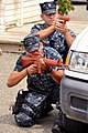 US Navy 100525-N-7764M-112 Master-at-Arms Seaman Recruit Hector Ramirez and Master-at-Arms 3rd Class Gerald Provost crouch behind a truck while training in an active-shooter scenario at Naval Station Guantanamo Bay.jpg