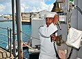 US Navy 100804-N-5006D-005 Seaman Apprentice Adam McMahon prepares to ring the ship's bell and announce the departure of Rear Adm. Doug McAneny.jpg