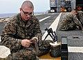 US Navy 101006-N-8113T-006 Lance Cpl. Richard Pobocik loads ammunition rounds for an M-240 machine gun qualification aboard USS Denver (LPD 9).jpg