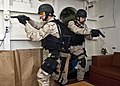 US Navy 110927-N-FI736-156 Fire Controlman 2nd Class Anthony Ferretti, left, and Fire Controlman 2nd Class Jody Powell clear a room during a visit.jpg