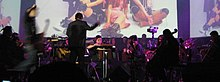 An orchestra performs a concert in a musical theatre, featuring music from the video game; in front of a screen showing people dressed as characters from the game.