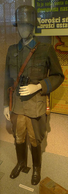 a colour photograph of a glass display case containing a uniform on a mannequin