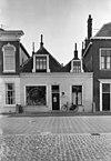 foto van Twee huizen (afzonderlijke kappen) met gecombineerde lijstgevel. Dakkapellen met vleugelstukjes. Winkelpui