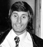 A man with dark hair is wearing a white shirt with a tie and a black jacket.