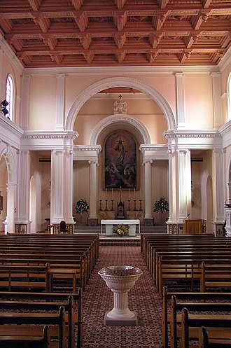 Sacred Heart Cathedral, Wellington - Sacred Heart Cathedral: interior (c. 2005) with baptismal font in cross-aisle (approximate site of tomb of Bishop Viard is to the left of the font); Painting and emblem of the Sacred Heart in the Sanctuary.