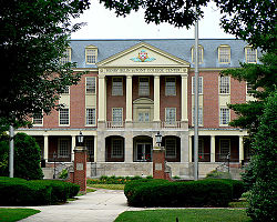 A brick neoclassical building fronted by four light-toned columns, with a green lawn and sidewalk in the foreground