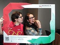 Wikimania 2015-Tuesday-Carmen Alcázar eating a stroopwafel and Andrés Cruz y Corro looking like ehhhh.jpg